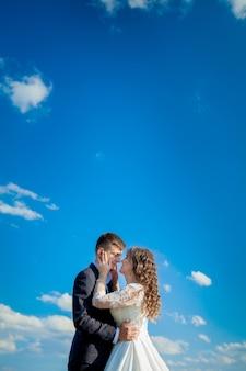 Les nouveaux mariés sur le mur de ciel bleu.photo de mariage.