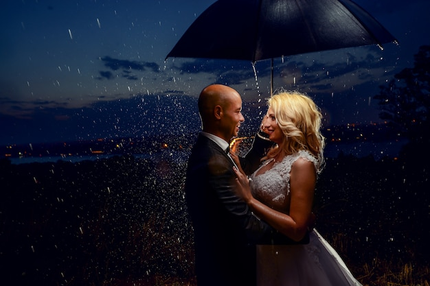 Les nouveaux mariés avec un parapluie sous la pluie