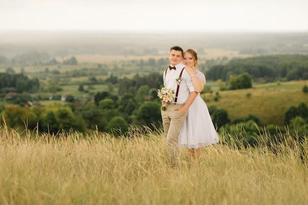 Les nouveaux mariés s'embrassent et regardent, contre un beau paysage.