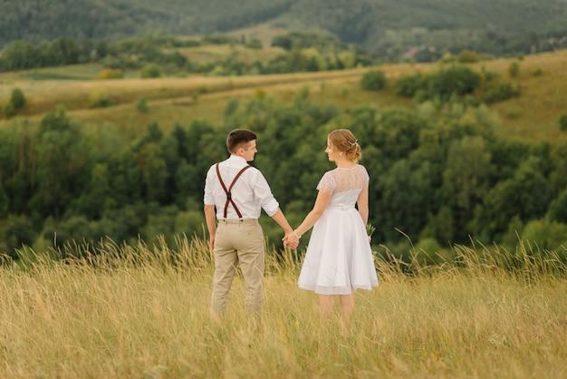 Les nouveaux mariés se regardent en se tenant la main contre la belle nature.