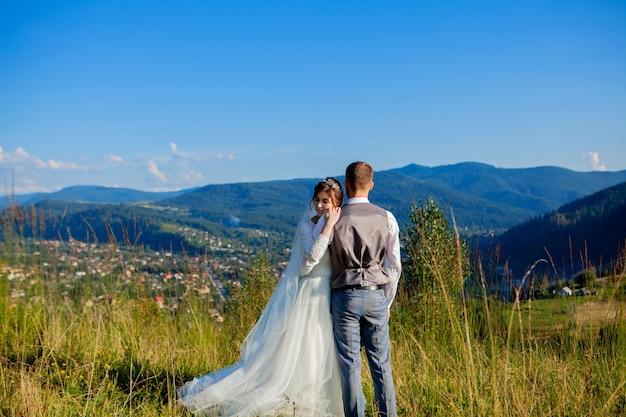 Les nouveaux mariés se sourient et s'embrassent dans la prairie au sommet de la montagne