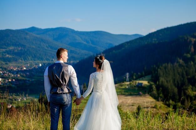 Les nouveaux mariés se sourient et s'embrassent dans la prairie au sommet de la montagne.