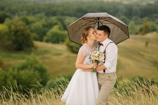 Les nouveaux mariés sont debout contre un beau paysage avec un parapluie. belle mariée embrasse le marié sur la joue