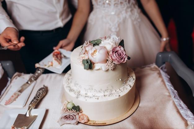 Les nouveaux mariés vont goûter le gâteau de mariage