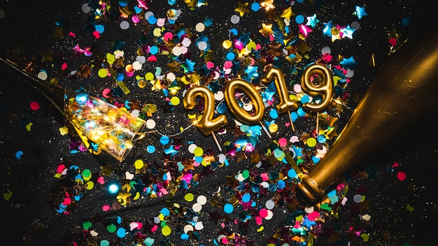 Nouvel an 2019 en forme de bougies sur une pile de confettis