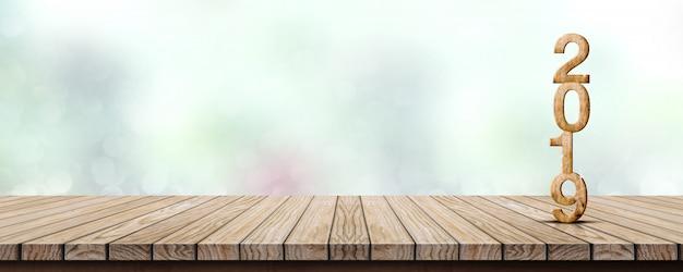 Nouvel an 2019 sur une table en bois au flou abstrait bokeh vert
