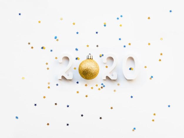 Nouvel an 2020 fond avec des confettis boule et étoile d'or.