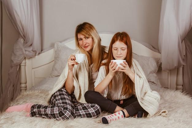 Nouvel an 2020. maman et sa fille aux cheveux roux sont assises sur le lit et boivent du cacao avec de la mousse. couvert d'une couverture, câlin.