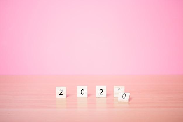 Nouvel an 2021 avec cube de bois sur fond rose.