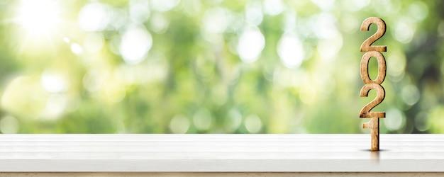 Nouvel an 2021 numéro de bois blanc sur table en bois à flou abstrait arbre vert bokeh