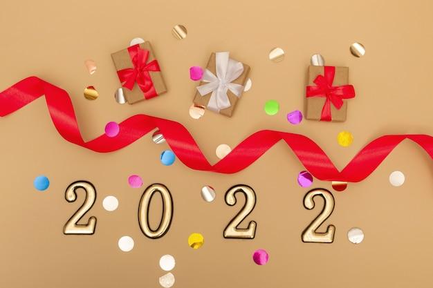 Nouvel an 2022. maquette du nouvel an vue de dessus sur fond beige : ruban rouge, coffret cadeau, chiffres en or et paillettes multicolores. mise en page de cartes postales, invitations.