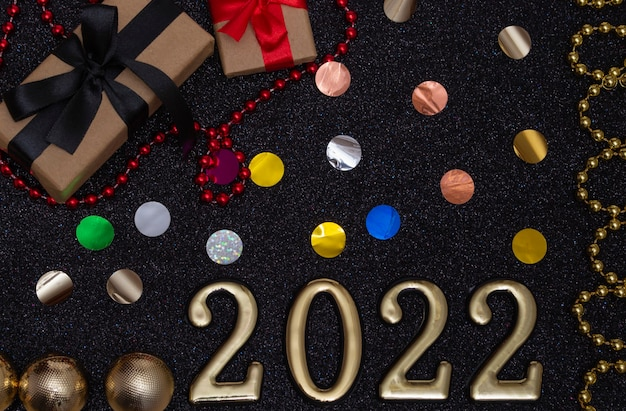 Nouvel an 2022. maquette du nouvel an vue de dessus sur fond noir brillant : ruban rouge, boîte-cadeau, numéros d'or et paillettes multicolores. mise en page de cartes postales, invitations.