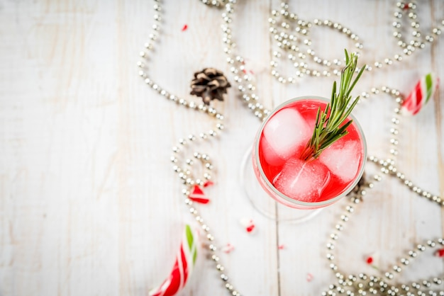 Nouvel an, boissons de noël. cocktail d'alcool rouge avec canneberge, liqueur, romarin, avec glace. sur une table blanche, avec des bonbons de noël, des ornements et des pommes de pin. vue de dessus du fond
