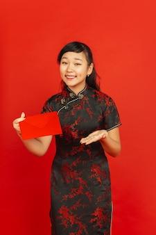 Nouvel an chinois 2020. portrait de jeune fille asiatique isolé sur fond rouge. modèle féminin en vêtements traditionnels a l'air heureux, souriant et montrant une enveloppe rouge. célébration, vacances, émotions.