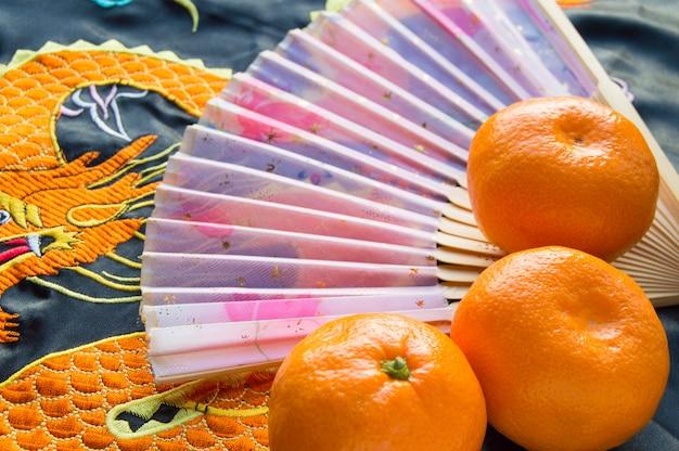 Nouvel an chinois, mandarines et éventail posés sur le tissu en soie orné d'un dragon brodé