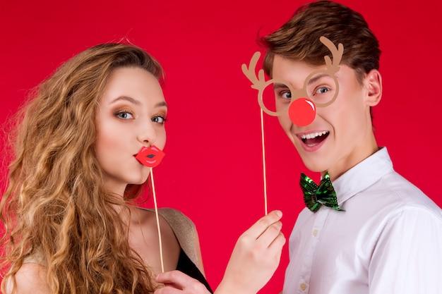 Nouvel an fête concept heureux amusement souriant amis couple hipster portant fée carnaval costume noeud papillon noël tenant une photo accessoires lèvres cerf corne lunettes célébrant les vacances d'hiver