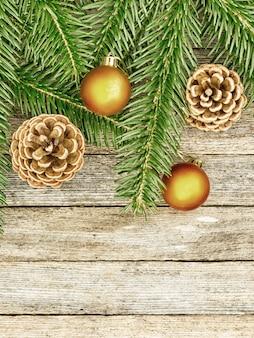 Nouvel an ou fond de noël: branches de sapin, cônes de boules de verre goldish sur fond de vieux bois, vue de dessus, espace copie, photo teintée