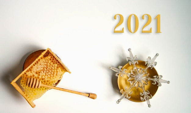 Nouvel an nid d'abeille jaune cassé avec du miel sur la table. texte 2021