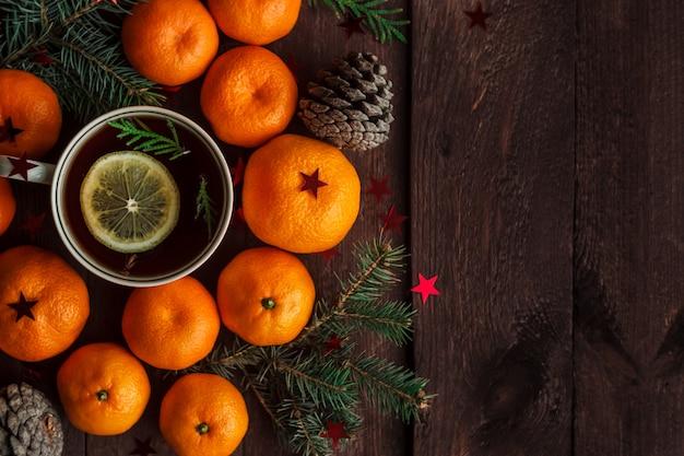 Nouvel an de noël avec des mandarines, du thé et des bonbons sur la table. hiver encore. mise au point sélective. fond