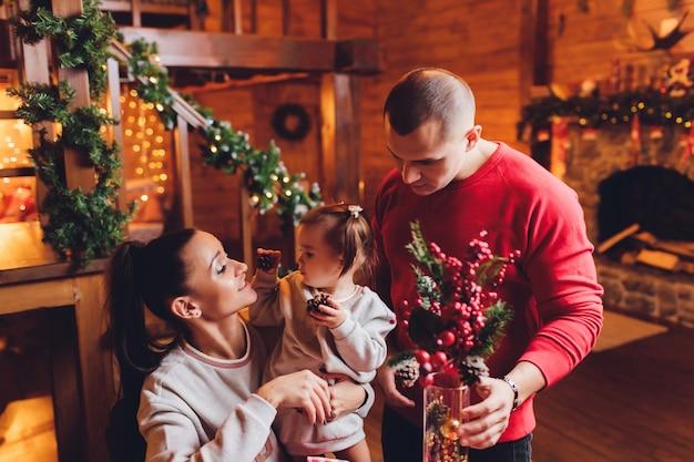 Nouvel an ou noël, portrait d'une belle famille, papa, maman et fille près de l'arbre du nouvel an, soirée de noël, famille tendre et heureuse en hiver, père tient sa fille dans ses bras.