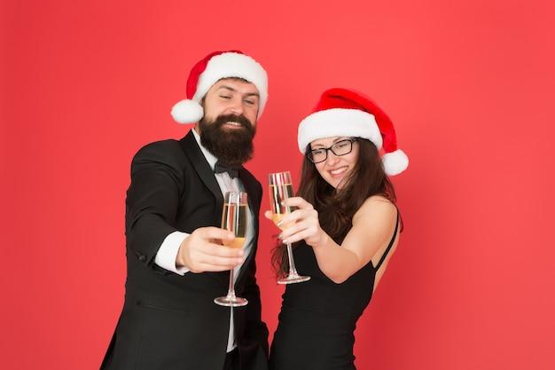 Nouvel an nouveaux objectifs. homme d'affaires et fille boivent du champagne. fête de noël. couple formel amoureux célèbre le nouvel an. smoking homme avec femme en bonnet de noel. joyeux noël et bravo à tous.