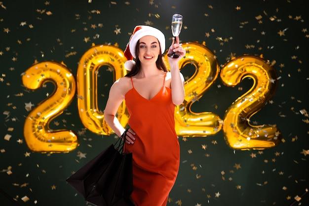 Nouvel an shopping femme de ballons d'or vendredi noir avec champagne et achète un bonnet de noel