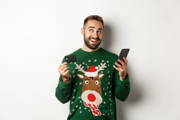 Nouvel an shopping en ligne et concept de noël jeune homme achetant des cadeaux sur internet tenant un téléphone mobile...
