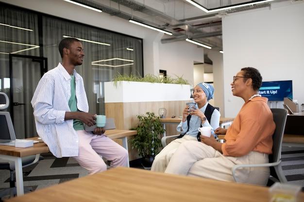 Nouvel employé masculin conversant avec des collègues féminines à son nouveau travail de bureau