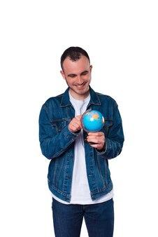 Nouvel endroit à visiter, heureux jeune bel homme pointant sur globe