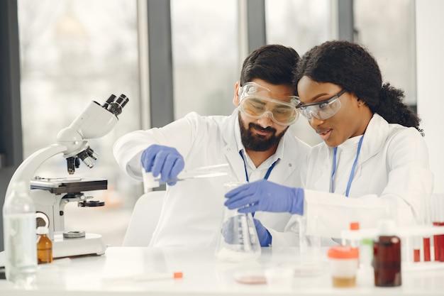 Nouvel essai. chercheurs qualifiés concentrés en uniforme. faire des tests, créer un vaccin.