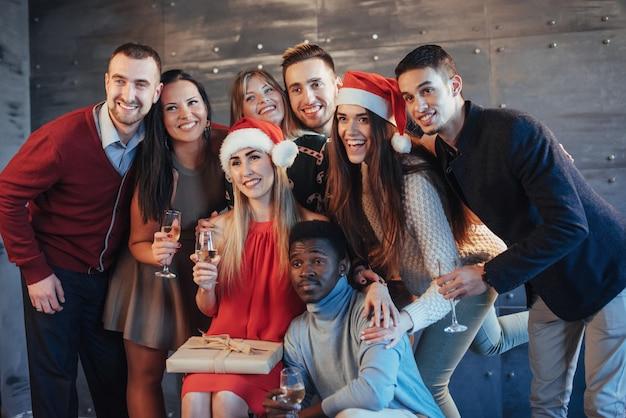 La nouvelle année arrive! groupe de joyeux jeunes multiethniques en chapeaux santa sur la fête, posant le concept de peuple lifestyle émotionnel