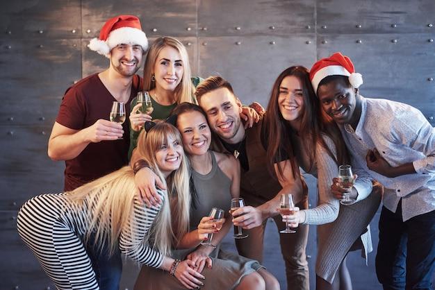 La nouvelle année arrive! groupe de joyeux jeunes multiethniques dans des chapeaux de santa sur la fête, posant le concept de personnes de style de vie émotionnel