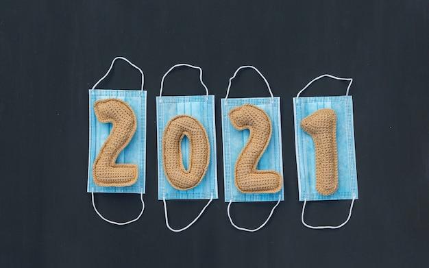Nouvelle année dans le contexte du coronavirus tricoté numéros 2021 sur un masque médical à bord de la craie