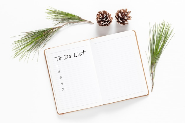 Nouvelle année. décorations de vacances et cahier avec liste de souhaits sur tableau blanc, style plat. notion de planification. mise à plat.
