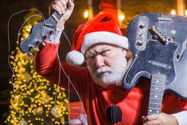 Nouvelle année. mauvais père noël. père noël avec guitare cassée. déguisement de père noël. période de noël. noël. roche. guitare électrique.