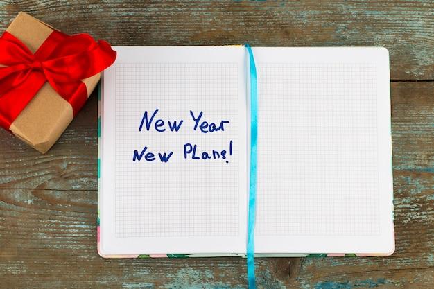 Nouvelle année, nouveau plan - texte sur bloc-notes avec cadeau. motivation commerciale, concepts d'inspiration.