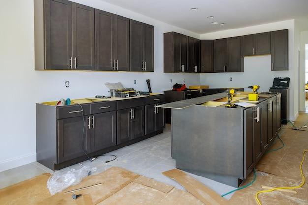 Nouvelle armoire dans une vue de cuisine de rénovation installée du meuble de base d'installation le tiroir dans l'armoire.