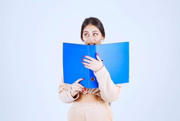 Nouvelle assistante cachant son visage derrière un dossier bleu