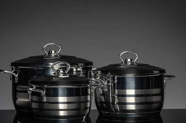 Nouvelle batterie de cuisine sur fond noir, vue de face