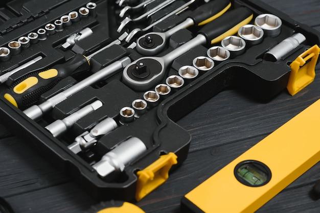 Nouvelle boîte à outils carrée noire sur fond de texture en bois. vue de dessus