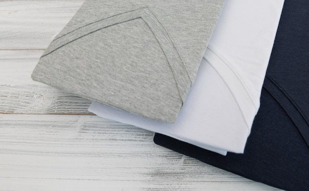 Nouvelle chemise à col en v noir, blanc et gris sur fond en bois blanc