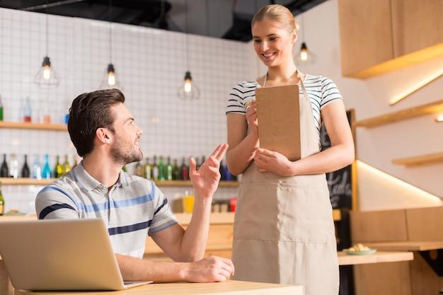 Nouvelle commande. joyeuse serveuse positive sympathique tenant des notes et souriant tout en écoutant la commande de son client