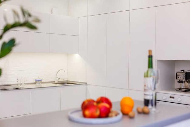 Nouvelle cuisine moderne équipée avec appareils électroménagers en acier inoxydable et bar pour le petit-déjeuner.
