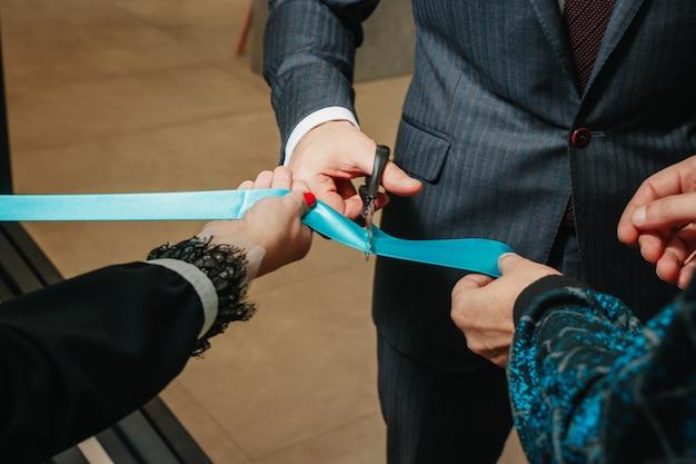 Nouvelle entreprise, ouverture, coupant un ruban bleu avec des ciseaux en gros plan.