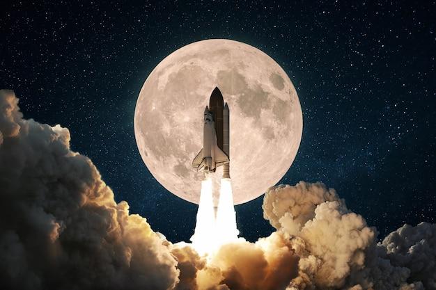 Une nouvelle fusée spatiale avec de la fumée et des nuages s'envole dans le ciel avec la pleine lune. décollage du vaisseau spatial de la navette. concept de lancement de mission spatiale.
