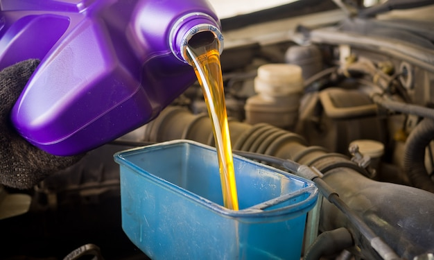 Nouvelle huile dans la voiture, verser de l'huile fraîche, station-service