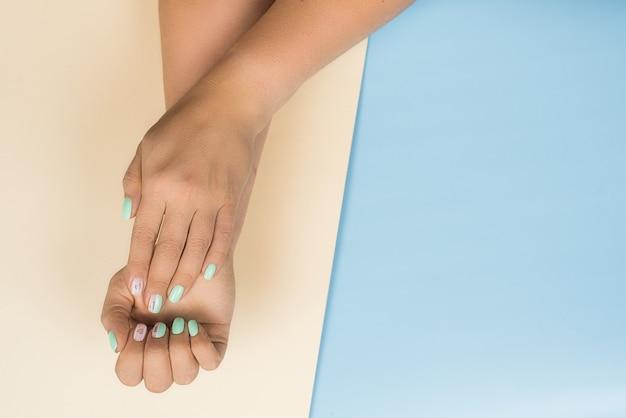 Nouvelle manucure bleue tendance féminine élégante avec des cœurs et les mots aiment sur les ongles. belle femme sur beige et bleu