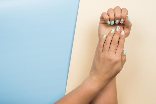 Nouvelle manucure bleue tendance féminine élégante avec des cœurs et les mots aiment sur les ongles. mains de la belle jeune femme sur pastel beige et bleu