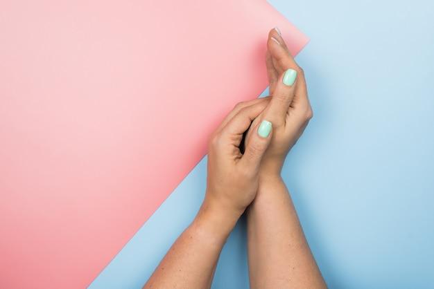 Nouvelle manucure bleue tendance féminine élégante. mains de la belle jeune femme sur pastel rose et bleu