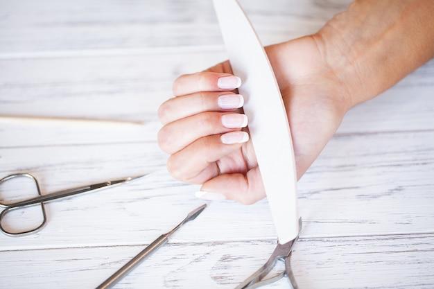 Nouvelle manucure. vue latérale du processus de manucure en salon. manucure professionnel fournit un service au client